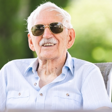 man smiling on sunny day with sunglasses on
