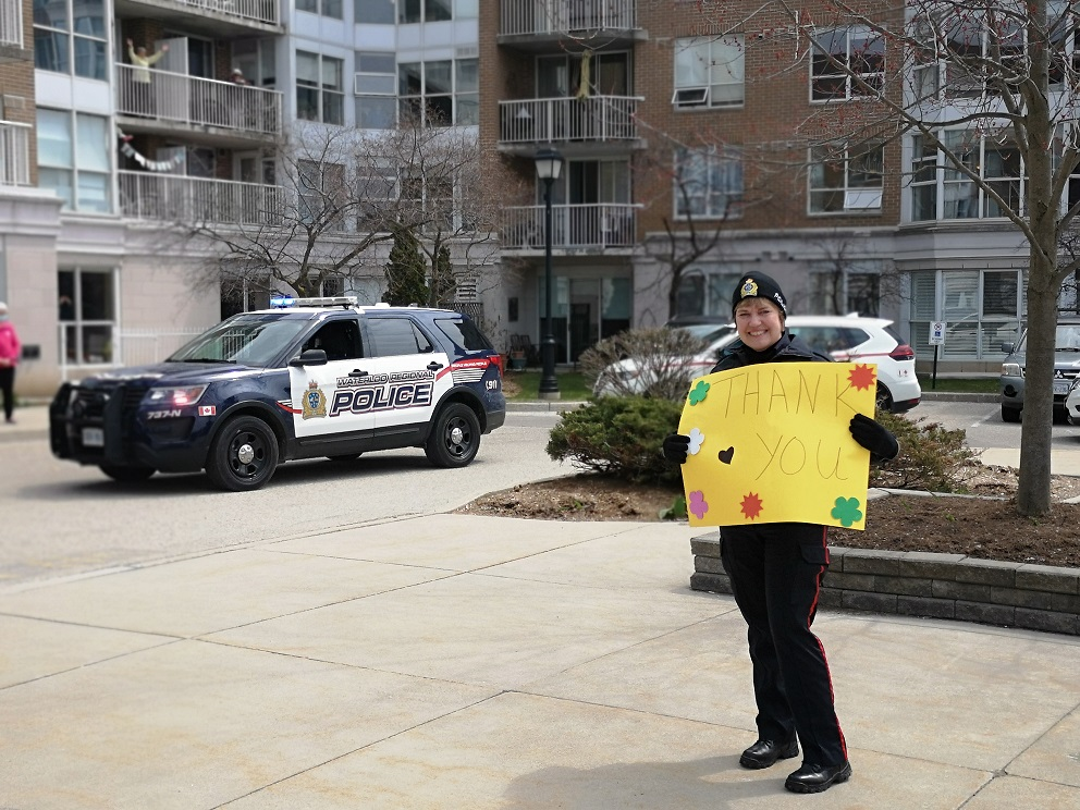 Police officer holding a thank you sign for our front line workers outside of our community
