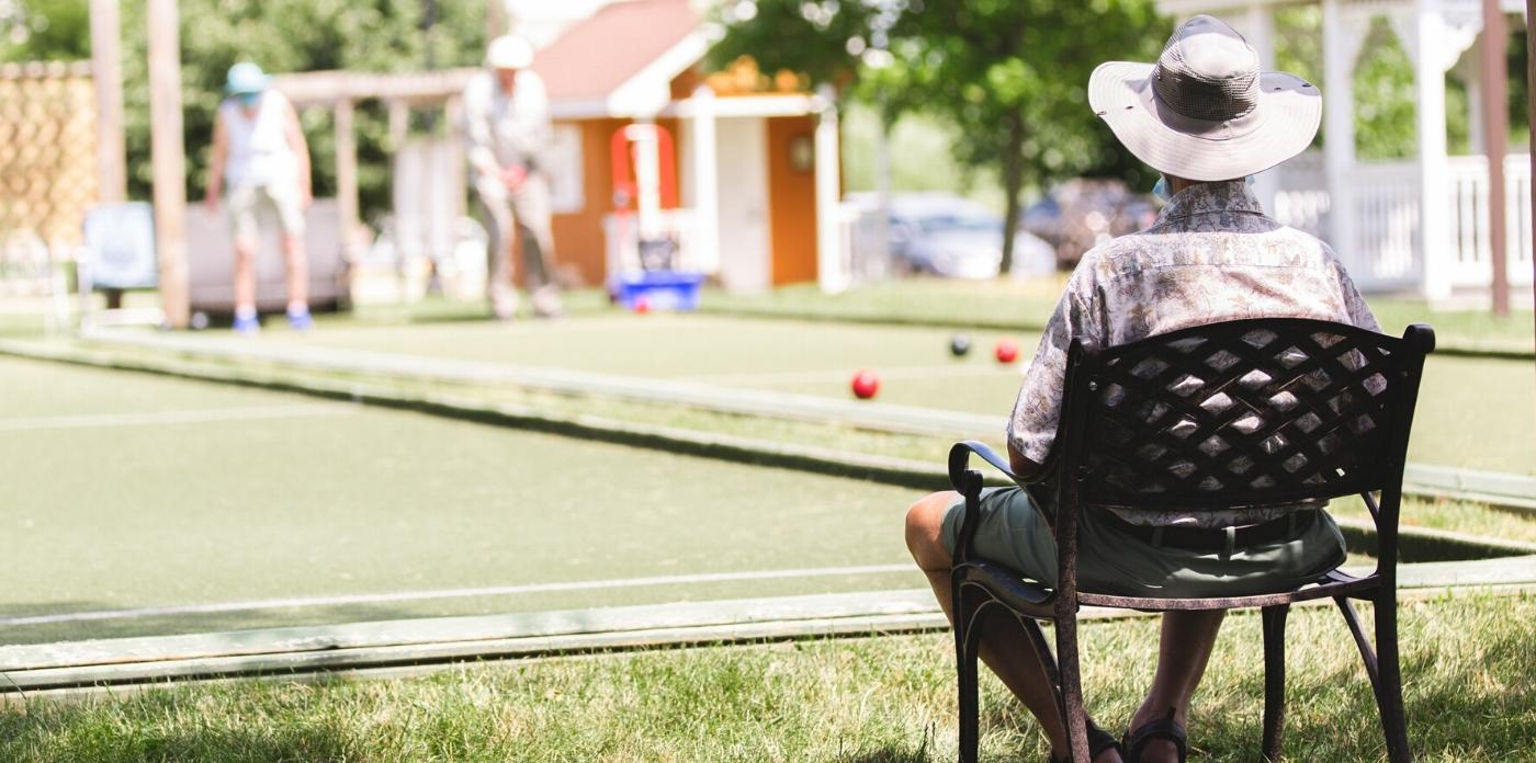 man sitting watching friends play bocce ball