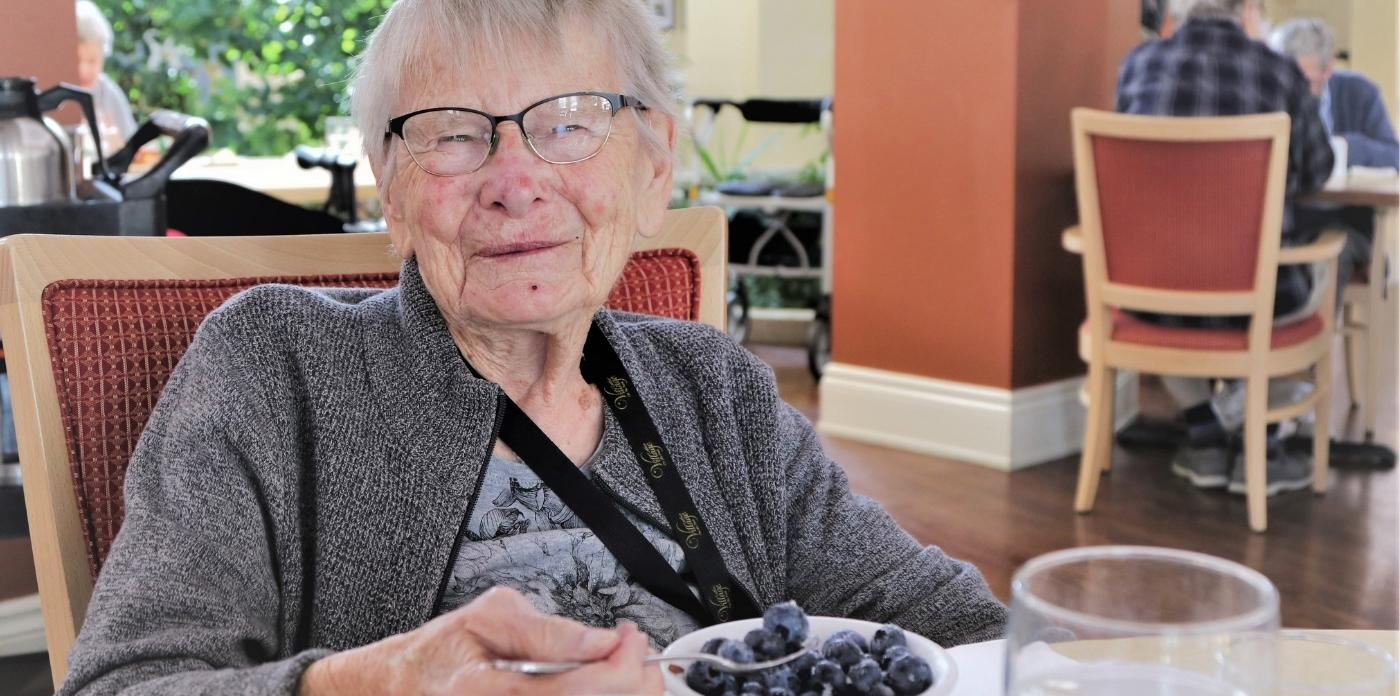 women smiling while eating blue berries